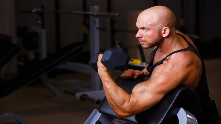 Bald bodybuilder exercising